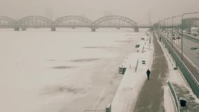 Man walking in winter riverside, filmed from a drone moving away in front of it 1080p, 25fps. Man walking on a river side, in winter, in the city of Riga. Shot stock video footage