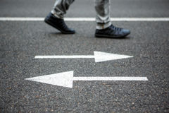 Man walking on the road with arrows Royalty Free Stock Images