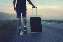 Man Walking on the Road Holding Black Luggage during Sunset stock photography