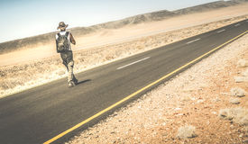 Man walking on the road on namibian african desert. Alternative lifestyle concept and wanderlust experience with guy backpacking to unknown - Travel trip stock photo