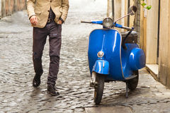 Man walking in Rome. Trendy man walking in Rome towards a vintage scooter Royalty Free Stock Images