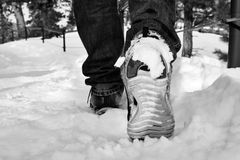 Man walking in running shoes on snow path (in black and white) Royalty Free Stock Photos