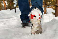 Man walking in running shoes on snow path Stock Photo