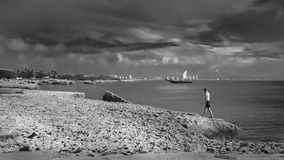 Man walking with a sailboat anchored as a background. Aruba, Caribbean - September 25, 2012: Man walking with a sailboat anchored as a background. The image was Royalty Free Stock Images