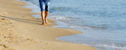 Man walking on sand beach Royalty Free Stock Photography