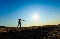 A man walking on sand desert Stock Image