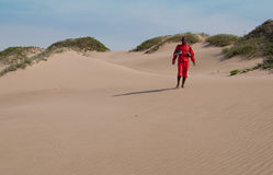 Man walking on sand dunes Royalty Free Stock Images