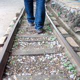 Man walking in sandals across train tracks Royalty Free Stock Image