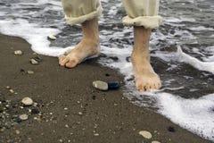 Man walking on sea shore. Man walking barefoot in water on sea shore Stock Image