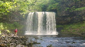 Man walking by Sgwd yr Eira Waterfall, Brecon Beacons National Park stock footage