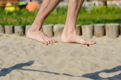 Man walking on the sling. Young man balancing on slackline at a beach Royalty Free Stock Photography