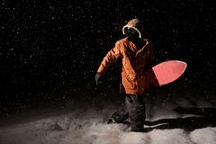 Man walking with the snowboard in the mountain resort in the nig royalty free stock images