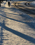Man walking on snowy pavement Royalty Free Stock Images