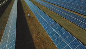 Man walking at solar power plant. Shot on drone. Man inspecting power plant. Male passes solar energy station. Engineer walking along solar panels. Generation of stock video footage