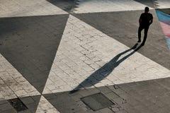 Man walking in square. Man walking in sunset casting long shadow Stock Photos