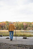 Man walking with a stick Stock Photography
