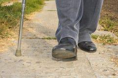 Man with walking stick doing hard step Stock Photos