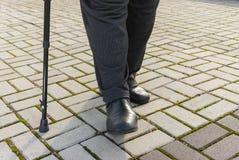 Man with walking stick doing hard step Royalty Free Stock Image