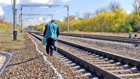 Man with walking stick and green suitcase walking beside railway. Lonely senior man with walking stick and green suitcase walking beside railway at autumnal stock video