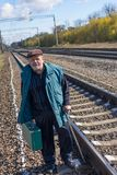 Man with walking stick standing near railway and holing an old green suitcase Stock Photography