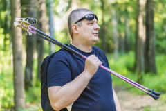 Man with walking sticks on the forest trail. On a sunny day Royalty Free Stock Image
