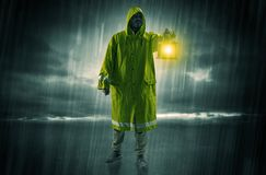 Man walking in storm with lantern. Raincoated man walking in storm with glowing lantern in his hand stock illustration