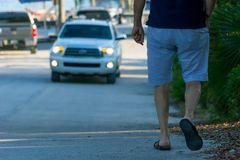 Man Walking on the Street on Blur Car Background. Destin Beach, Florida. Man Walking on the Street on Blur Car Background. Destin Beach royalty free stock images