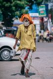 Man Walking on Street Carrying Metal Bucket Royalty Free Stock Images