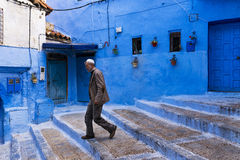 Man walking in a street of the town of Chefchaouen in Morocco. Royalty Free Stock Images