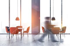 Man walking in stylish restaurant. Businessman walking in minimalistic restaurant interior with white walls, large windows and square tables with orange chairs royalty free stock images