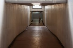 A man walking in the subway. A man walking in the distance of a brightly lit subway Stock Photos