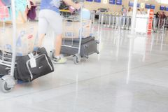 Man walking suitcase luggage bag on trolley in the airport. Blurred motion selective stock images