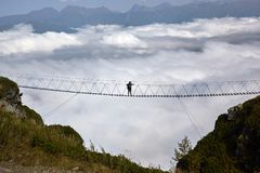 Man walking on suspension bridge and looking at cloudy mountains below. Royalty Free Stock Image