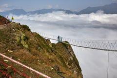 Man walking on suspension bridge and looking at cloudy mountains below. royalty free stock image