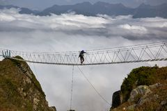 Man walking on suspension bridge and looking at cloudy mountains below. stock images