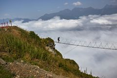 Man walking on suspension bridge and looking at cloudy mountains below. Royalty Free Stock Photo