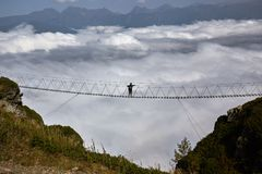 Man walking on suspension bridge and looking at cloudy mountains below. Stock Photos