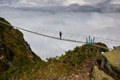Man walking on suspension bridge and looking at cloudy mountains below. Stock Image