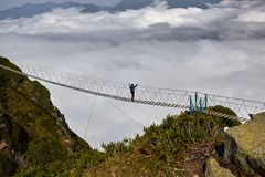 Man walking on suspension bridge and looking at cloudy mountains below. stock photography