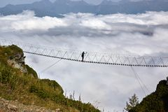 Man walking on suspension bridge and looking at cloudy mountains below. stock photo