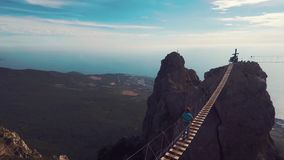 Man walking suspension bridge to Cross in Crimea. Ay Petri stock footage