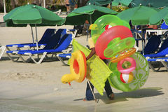 Man walking with swim matresses and rings, Boca Chica beach Royalty Free Stock Images