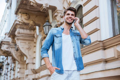 Man walking and talking on cell phone in the city. Cheerful young man walking and talking on cell phone in the city Royalty Free Stock Image