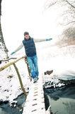 Man walking on the thin foot bridge Stock Photo