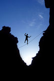 Man walking on tight rope over the rock Stock Photo