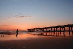 Man walking time on the beautiful beach at sunrise. Royalty Free Stock Photo