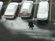 Man walking to car in snow. Stock Image