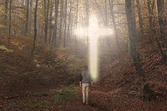Man walking to the cross in a forest during autumn. Man walking to a Christian Cross of light stock images