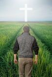 Man walking to the cross in a green field. Man walking to a Christian Cross of light stock photos