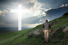 Man walking to the cross in a green field. Man walking to a Christian Cross of light royalty free stock images